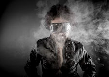 Driver, biker with sunglasses era dressed Leather jacket, huge s. Moke over dark background Stock Photography