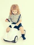 Driver biondo del bambino piccolo isolato su bianco Immagini Stock