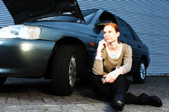 Driver With a Broken Car. A young female driver having car troubles and sitting next to her car. She has just called for help and the mobile phone is in her hand royalty free stock images