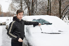 Driver with brush cleans car from snow Royalty Free Stock Image