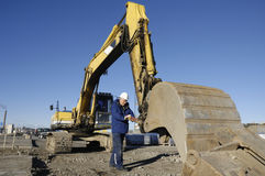 Driver and bulldozer. Large bulldozer, digger, scoop being examined by driver, trademarks removed Stock Photo