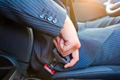 Driver  in business suit fastens his seat himself automobile seat belt Royalty Free Stock Photography