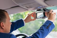 Driver businessman adjusts rear view mirror in car interior royalty free stock images