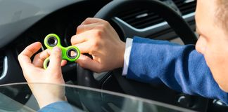 The driver of the car holds a spinner in his hand, to soothe Royalty Free Stock Photography