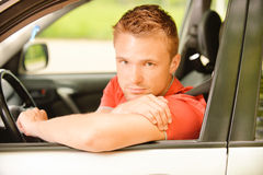 Driver of car looks. Young man-driver in red clothes at wheel car Stock Photos