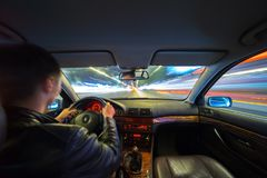 Driver in car moves at fast speed at night. Driver in a car moves at fast speed at the autum night. Blured road with lights with car on high speed Stock Images