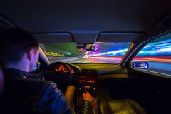 Driver in car moves at fast speed at night. Driver in a car moves at fast speed at the autum night. Blured road with lights with car on high speed Royalty Free Stock Photos