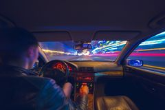 Driver in car moves at fast speed at night. Driver in a car moves at fast speed at the autum night. Blured road with lights with car on high speed Stock Photography