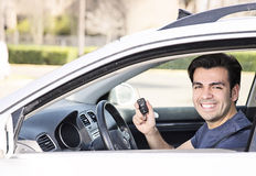 Driver in car showing keys. Hispanic car driver smiling showing new car keys and car royalty free stock photos
