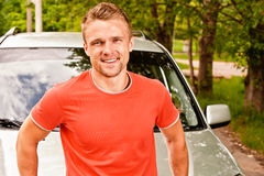 Driver of car smiles. Driver of car stands about cowl and smiles against summer nature royalty free stock image