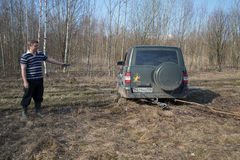 Driver of the car UAZ-Patriot pulls out dirt jammed machine Stock Photo