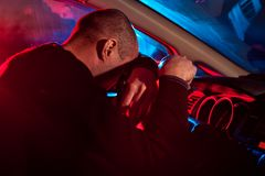 Driver is caught driving under alcohol influence. Young male driver is caught driving under alcohol influence. Man covering his face from police car light Stock Photos
