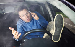 Driver and cellphone. Driver during conversation on cellphone does not care about road so much that he has lift his foot royalty free stock photo