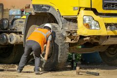 Driver changes the blown wheel on the construction site royalty free stock images