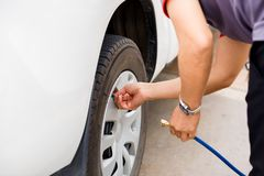 Driver checking air pressure and filling air in the tires close up stock photos