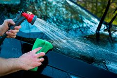 Driver cleaning auto, automobile windows. Transportation self service, care concept. Car service. A man wash a hood of stock photography
