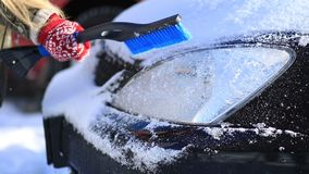 Driver cleaning car headlights from snow stock footage