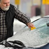 Winter scene, driver cleaning windshield og car Royalty Free Stock Photos