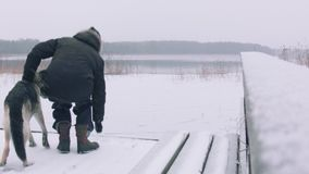 Man An Dog In Winter. Man and dog on a pier in snowy weather, frosty winter scene stock footage