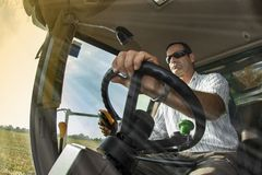Viewpoint of the driver of the combine on the corn field Stock Images