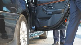 Driver coming to car and opens door for businessman. Chauffeur uncover door of automobile for male passenger. Business. Man with briefcase get out from auto and stock footage