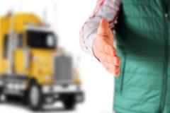 Driver con un saluto aperto della mano Camion giallo dietro lui Immagine Stock