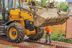 Driver at the construction site washes the excavator on the overpass stock photo