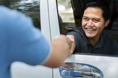 Driver and costumer or friend shake hand in sunny day royalty free stock images