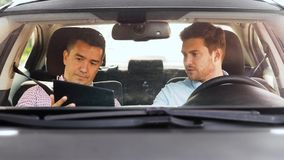 Man with driving school instructor talking in car stock video footage