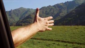 Driver degli uomini che ritiene il vento tramite le sue mani mentre guidando nel lato del paese archivi video