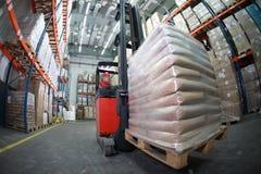 Driver del carrello elevatore che trasporta i sacchi in magazzino Immagine Stock