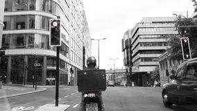 Driver delivery scooter in London black and white. London, United Kingdom - Circa 2017: Delivery courier on small motorcycle scooter waiting at interaction red stock video