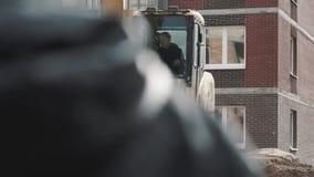 Driver dell'escavatore che guida intorno nella cabina lustrata al cantiere, rallentatore archivi video