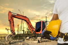 Driver dell'escavatore a cucchiaia rovescia che porta un casco nell'area della costruzione fotografia stock