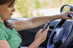 Driver della donna che legge un messaggio di testo fotografia stock libera da diritti
