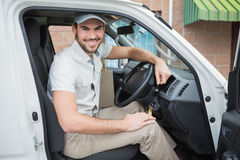 Driver di consegna che sorride alla macchina fotografica in suo furgone Fotografia Stock