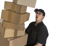 Driver di consegna con una pila di pacchetti Immagine Stock