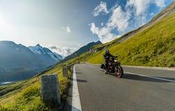 Driver di motociclo che guida l'incrociatore giapponese di alto potere in strada principale alpina su Hochalpenstrasse famoso, Au immagine stock libera da diritti