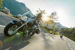 Driver di motociclo che guida l'incrociatore giapponese di alto potere in strada principale alpina su Hochalpenstrasse famoso, Au fotografie stock libere da diritti