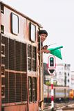The driver of a diesel train signaling with a green flag stock photography