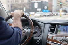 Driver Driving luxury vehicle down city street royalty free stock photo