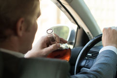Driver drinks alcohol driving a car Stock Images