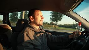 Drunk Driver. Danger on the road. The driver drinks alcohol at the wheel stock video footage