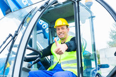 Driver driving  construction excavator Royalty Free Stock Image