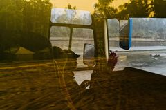 Man is driving a public coach isolated unique photo. A driver is driving a public coach with reflection of moving road in the glass unique photograph royalty free stock images
