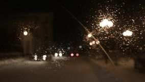 Driver driving on a rainy night in a city, view from inside. Footage. View from the windshield of the car in the rain.  stock footage