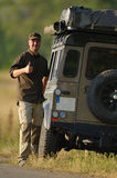 Driver and Expedition vehicle. Driver showing thumbs up and Land Rover Defender with expedition equipment Stock Photography