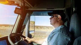 Driver& x27 för trafik för stor lastbil för lastbilsförare höger; s-händer på det stora lastbilstyrninghjulet royaltyfri bild