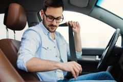 Driver fastening his seat belt in car stock photography