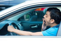 Driver fatigue. Closeup portrait tired young funny man in blue shirt with short attention span, driving his black car after long hours trip, yawning at wheel Royalty Free Stock Photography